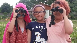 Fourth-grade students from Lincoln Elementary School, in Madison, Wisconsin, look through binoculars.