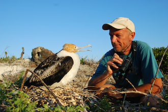 H. Weimerskirch with a juvenile Great Frigatebird, photo by Henri Weimerskirch CEBC CNRS.