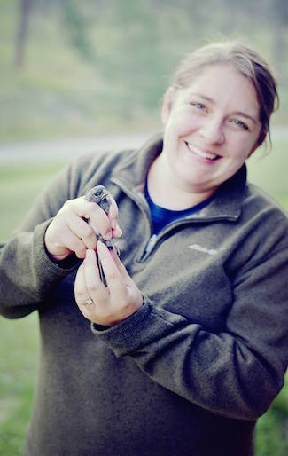 Bird educator Amber Schiltz holds a banded Lazuli Bunting. Photo courtesy Bird Conservancy of the Rockies