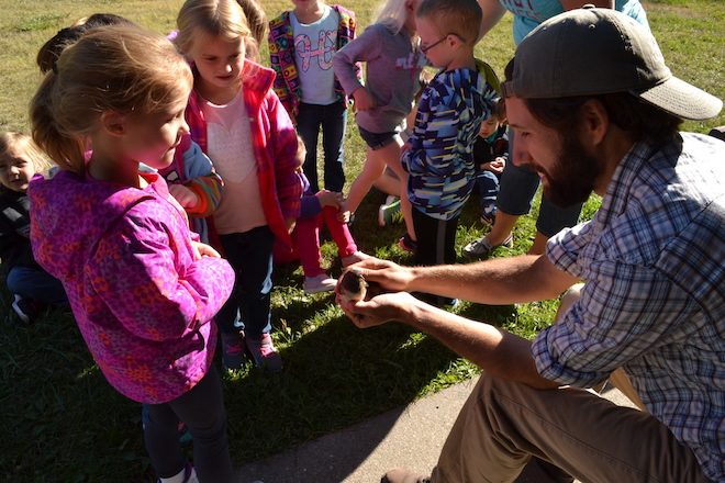 A bird bander shows a group of children a Spotted Towhee before releasing it. Photo courtesy Bird Conservancy of the Rockies