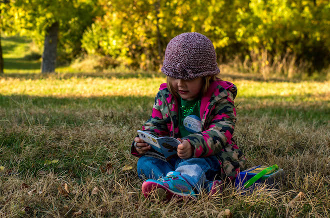 A young visitor to Chadron State Park examines a bird field guide. Photo courtesy Bird Conservancy of the Rockies
